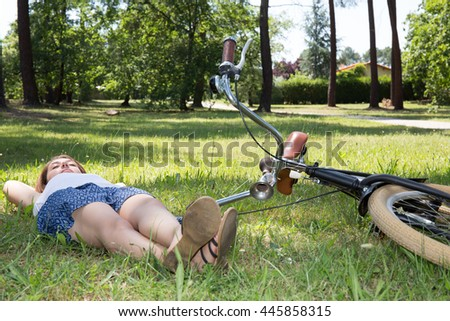 Young woman with a bike lying on the grass in a summer park
