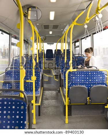 Young woman with a book alone on the bus - stock photo