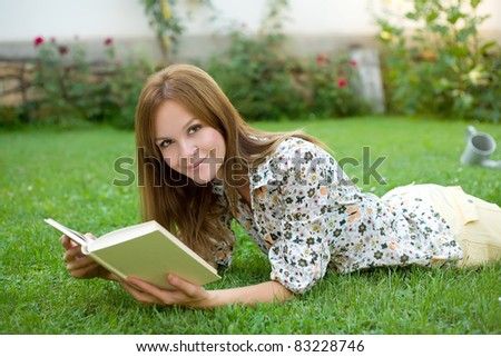 Young woman with a book on the grass