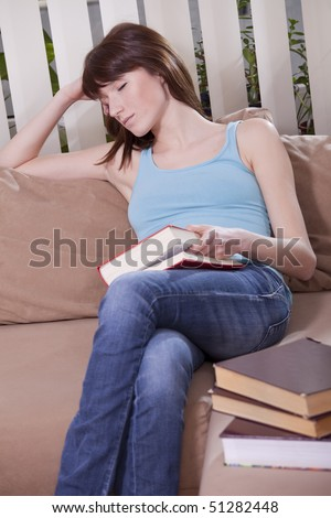 young woman with a book sleeping on the sofa