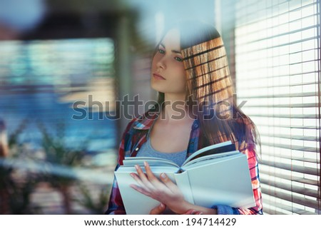 Young woman with a book standing near window; shot through window glass with reflections and flares - stock photo
