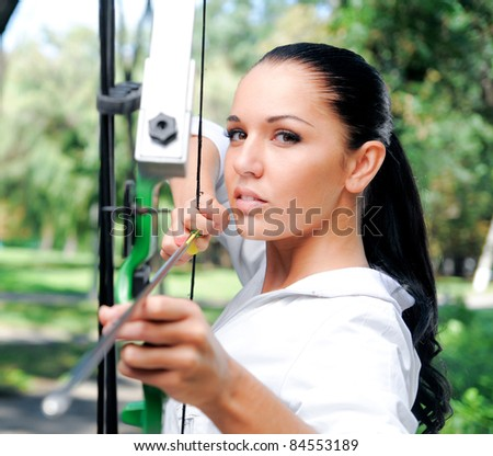 young woman with a bow and arrows in the woods