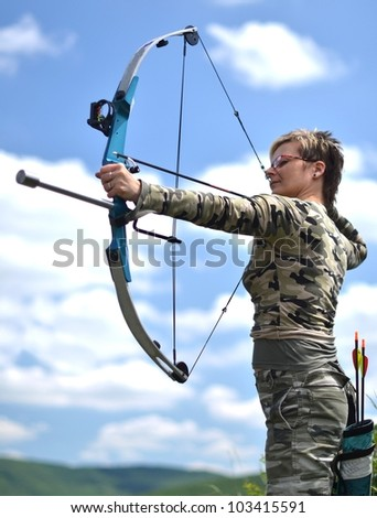 young woman with a bow and arrows on blue sky background - stock photo