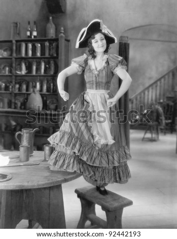 Young woman with a buccaneer hat dancing on a chair - stock photo