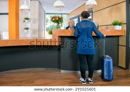 Young woman with a carry on bag at a check in desk, where a female attendant offers information and assistance - stock photo