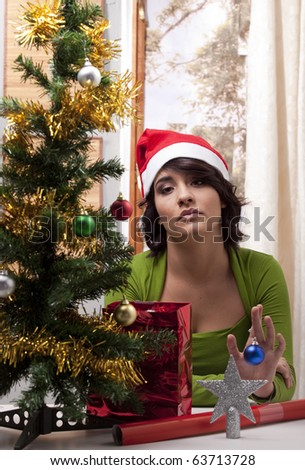 Young woman with a Christmas Santa hat looking lonely in her home with her Christmas tree. - stock photo