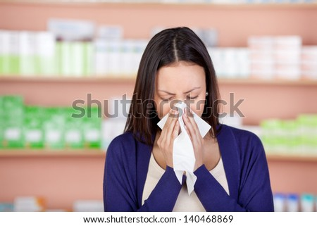 young woman with a cold using tissue in pharmacy - stock photo