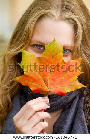 Young woman with a colorful maple leaf  - stock photo