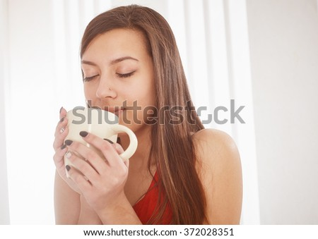 Young woman with a cup, closed her eyes to enjoy the drink. - stock photo