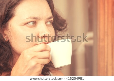 Young woman with a cup of coffee. Toned - stock photo