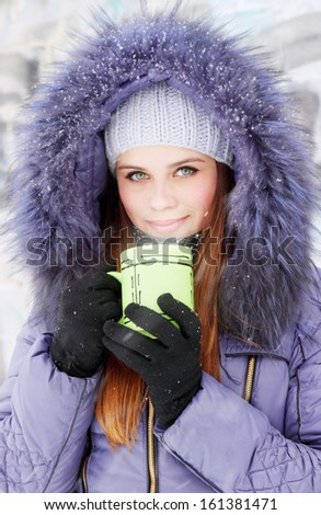 Young woman with a cup of hot drink - stock photo