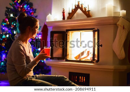 Young woman with a cup of hot winter drink enjoying Christmas eve by a fireplace at cozy living room - stock photo