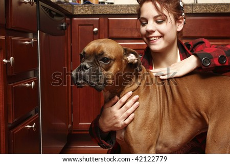 Young woman with a dog in the kitchen.