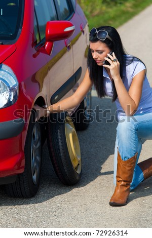 Young woman with a flat tire in car - stock photo