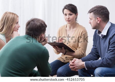 Young woman with a flipboard leading a discussion between a group of people sitting in a circle