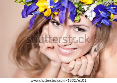 Young woman with a flower arrangement in her hair smiling at the camera