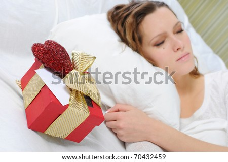 young woman with a gift box in the bed - stock photo