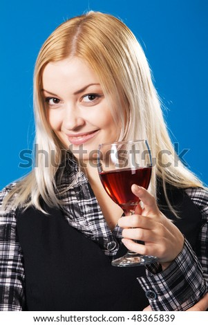 Young woman with a glass of red wine, blue background - stock photo
