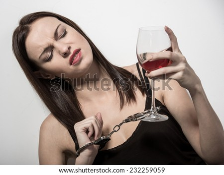 Young woman with a glass of wine and handcuffs.  Addicted to drugs and alcohol. - stock photo