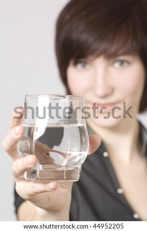 Young woman with a glass with transparent liquid in a hand - stock photo