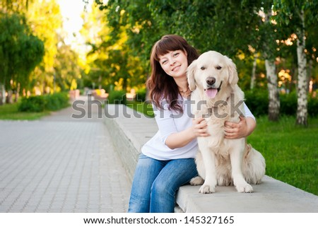 Young woman with a golden retriever in park - stock photo
