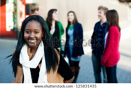 Young woman with a group of friends smiling outside - stock photo