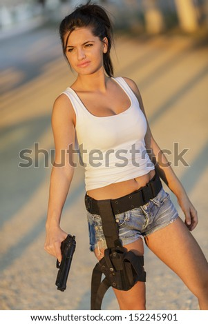 Young woman with a gun - stock photo