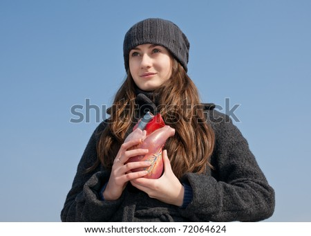 Young woman with a heart in her hand against the blue sky. Focus mainly on the face. - stock photo
