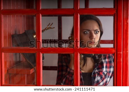 Young woman with a horrified expression peering out of the glass window pane on a public telephone booth as she chats on a vintage phone - stock photo