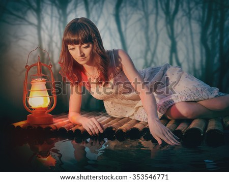 Young woman with a lantern floating on a raft in a dark scary forest. Princess in rural white dress in a fairy forest in vintage style.