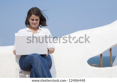 Young woman with a mac laptop in a mediterranean look terrace near the ocean