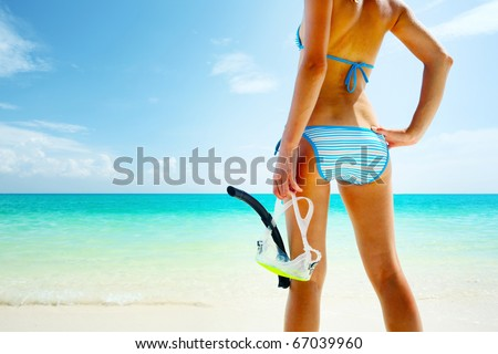 Young woman with a mask going to snorkel in clear sea - stock photo