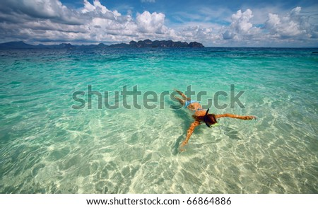 Young woman with a mask snorkeling in clear sea - stock photo