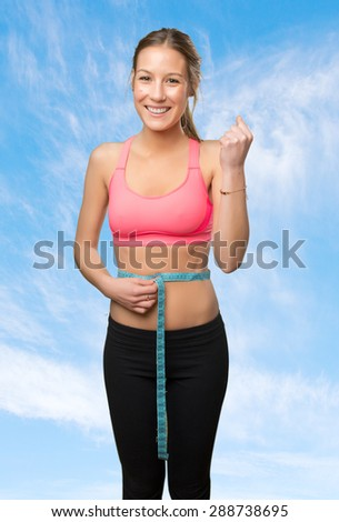 Young woman with a measurement scale in her belly. Over clouds background - stock photo