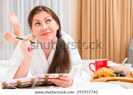 young woman with a notebook and breakfast in bed - stock photo