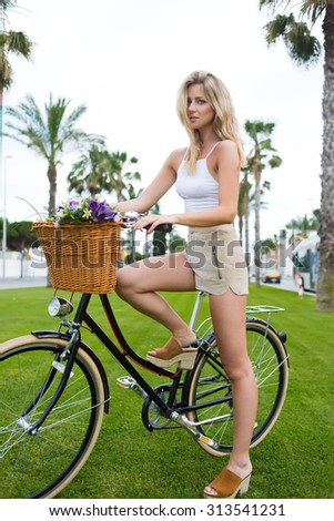 Young woman with a perfect figure stands with her retro bike in the park on green grass while enjoying a rest after riding, wonderful caucasian female posing outdoors for camera with classic bicycle - stock photo