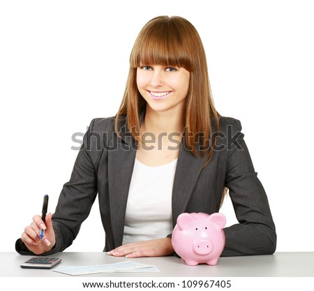 Young woman with a piggy bank and using a calculator, isolated on white background - stock photo