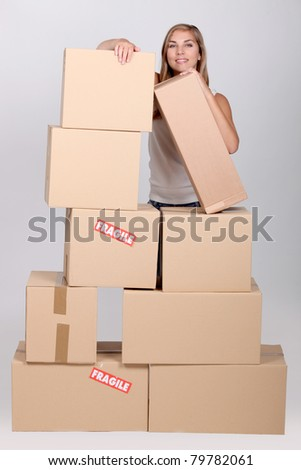 Young woman with a pile of cardboard boxes marked fragile - stock photo