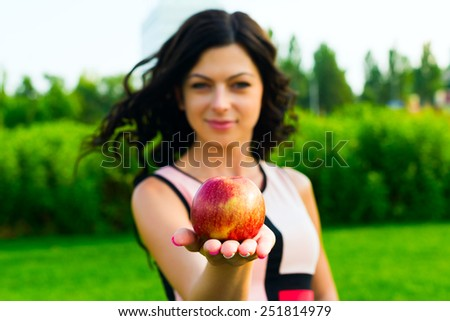 Young woman with a red juicy apple, on  green  background - focused on apple - stock photo