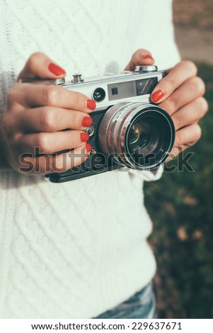 Young woman with a retro camera - stock photo