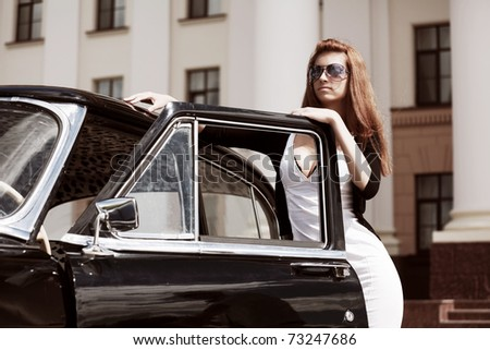 Young woman with a retro car