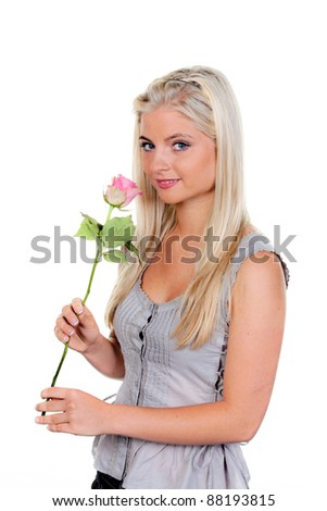 young woman with a rose at the smell it.