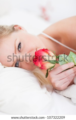 Young woman with a rose in a bed - stock photo
