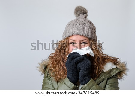 Young woman with a seasonal winter cold or flu wearing a furry jacket and knitted cap blowing her nose on a white handkerchief - stock photo