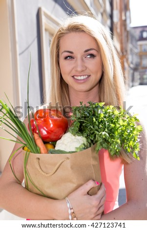 Young woman with a  shopping bag. vegetables - stock photo