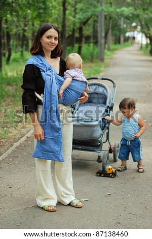 Young woman with a small child in a baby carrier and a toddler standing next to carriage - stock photo