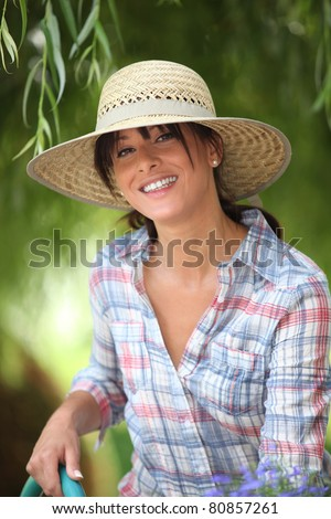 young woman with a straw hat is watering in her kitchen garden - stock photo