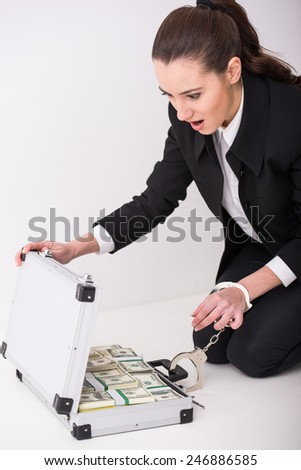 Young woman with a suitcase full of money and handcuffs. - stock photo