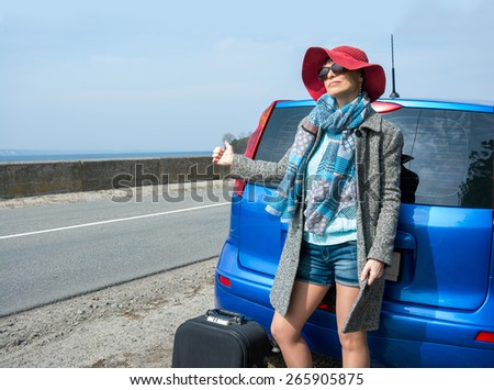 Young woman with a suitcase is hitchhiking on road near the sea pointing her thumb up - stock photo