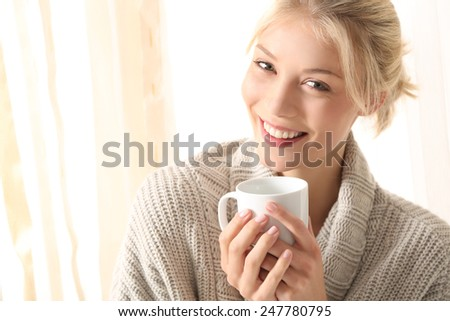 young woman with a tea cup in her hand - stock photo